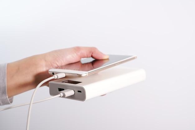 Les femmes tiennent main smartphone et chargeur, powerbank et téléphone intelligent se connecte