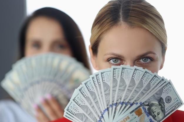 Les femmes tiennent un ventilateur de billets de cent dollars