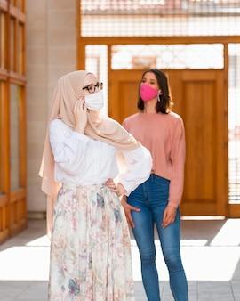 Femmes de tir moyen avec des masques médicaux