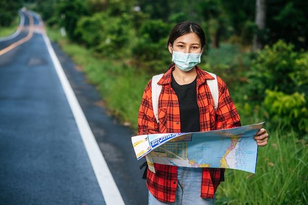 Les femmes touristes se lèvent et regardent la carte sur la route.