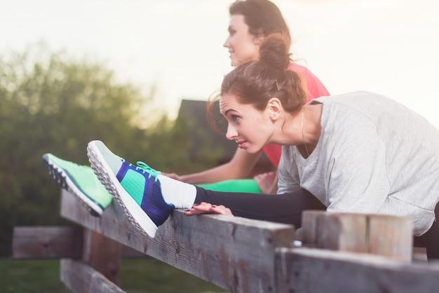 Femmes travaillant étirement des muscles des jambes du dos pour réchauffer les taches de rue préparation pour l'exécution de l'entraînement.