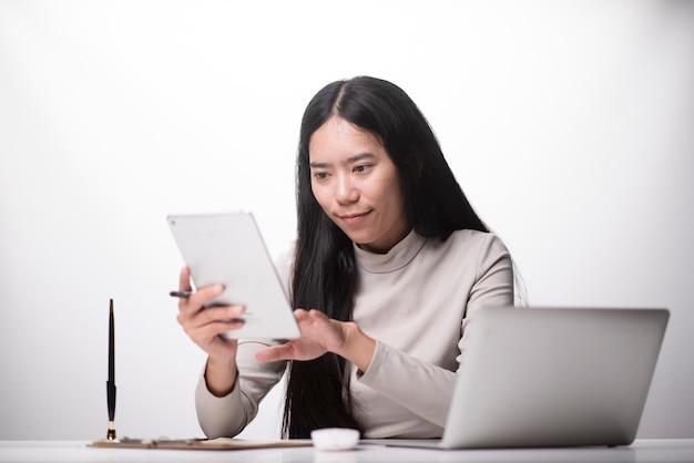 Femmes travaillant sur un ordinateur portable de la maison sur un plancher en bois avec colis postal, vente en ligne
