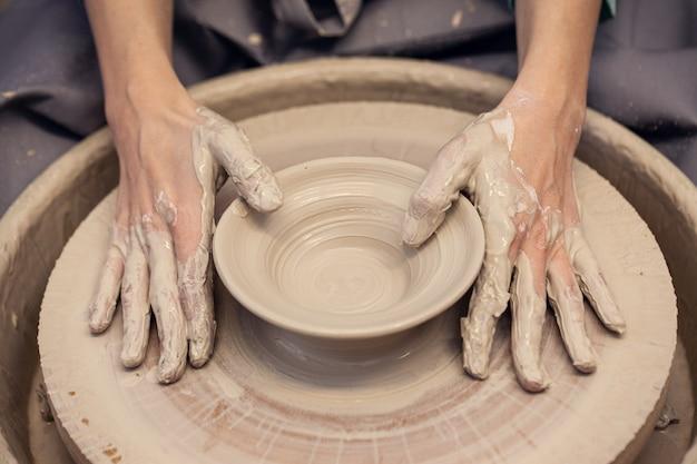 Les femmes travaillant sur le tour de potier se bouchent