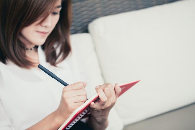 Femmes travailleuses asiatiques écrivant une note de projet d'entreprise note avec fond.