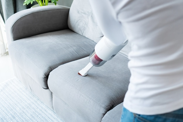 Les femmes utilisant un canapé de nettoyage aspirateur sans fil