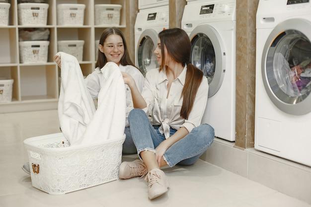 Les femmes utilisant une machine à laver font la lessive. jeunes filles prêtes à laver les vêtements. intérieur, concept de processus de lavage