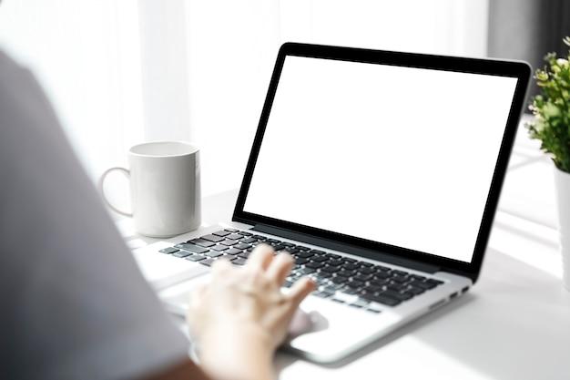 Femmes utilisant un ordinateur portable avec un écran vide à table dans le bureau, vue arrière des femmes d'affaires mains occupées à l'aide d'un ordinateur portable au bureau.