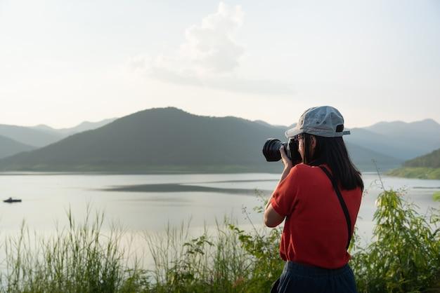 Les femmes utilisent l'appareil photo pour prendre des photos du tourisme de nature.