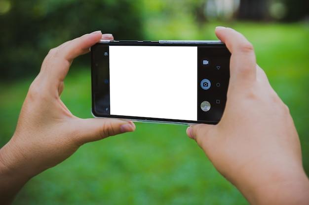 Les femmes utilisent le téléphone dans un parc verdoyant avec un écran blanc.