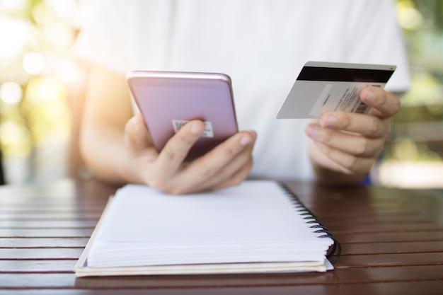 Les femmes utilisent le téléphone pour les services bancaires mobiles avec carte de crédit pour les achats en ligne