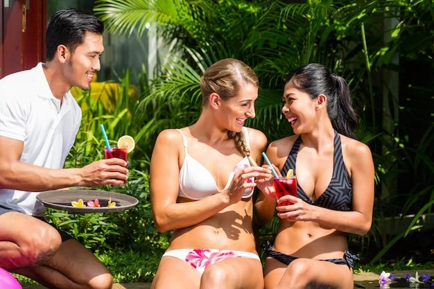 Femmes en vacances à la piscine d'un hôtel asiatique avec des cocktails