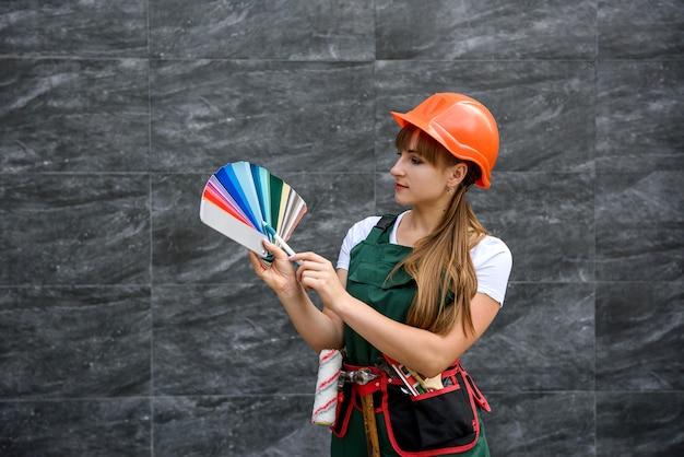 Femmes en vêtements de construction et casque avec échantillonneur de couleurs prêt à être réparé
