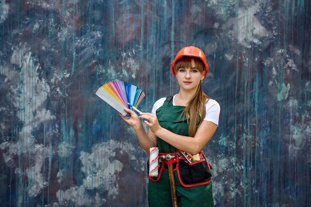 Femmes en vêtements de construction et casque avec échantillonneur de couleurs prêts à être réparés