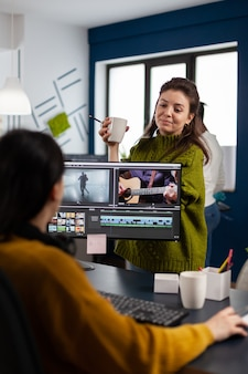 Des femmes vidéastes montent un projet vidéo créant du contenu, une équipe de blogueurs assis dans un studio de démarrage moderne