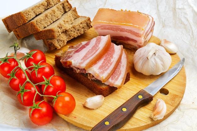Fendre du bacon salé avec des tomates cerises et de l'ail.