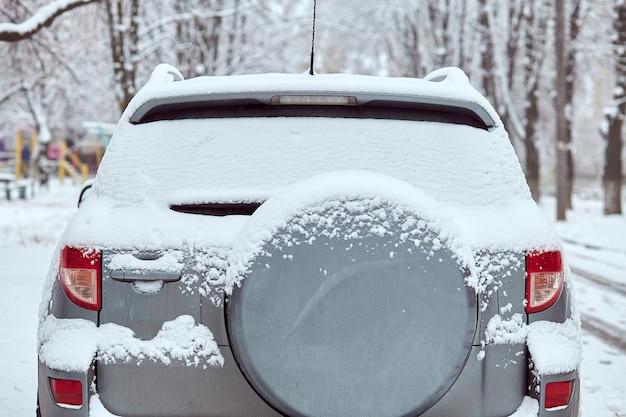 Fenêtre arrière de voiture grise garée dans la rue en journée d'hiver, vue arrière. maquette pour autocollant ou décalcomanies