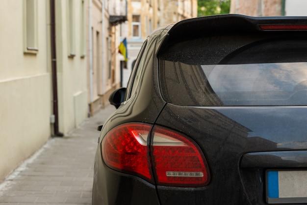 Fenêtre arrière d'une voiture noire garée dans la rue en été, journée ensoleillée, maquette de vue arrière pour autocollant ou décalcomanies