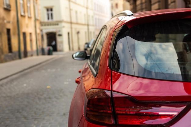 Fenêtre arrière de la voiture rouge garée dans la rue en été, journée ensoleillée, maquette de vue arrière pour autocollant ou décalcomanies