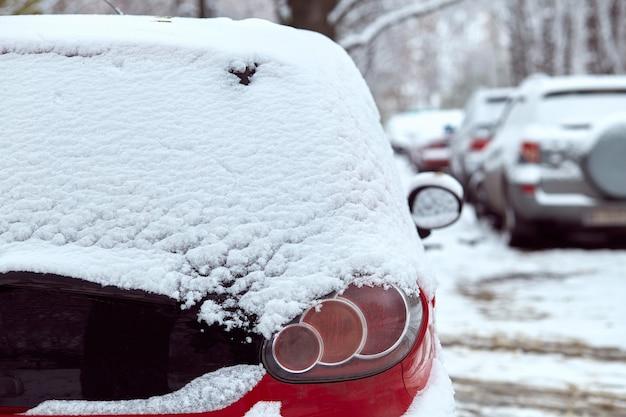 Fenêtre arrière de voiture rouge garée dans la rue en journée d'hiver, vue arrière. maquette pour autocollant ou décalcomanies