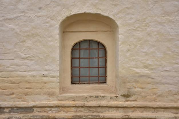 Fenêtre avec barres dans le mur de la forteresse, échappatoire avec barres, fenêtre dans le mur