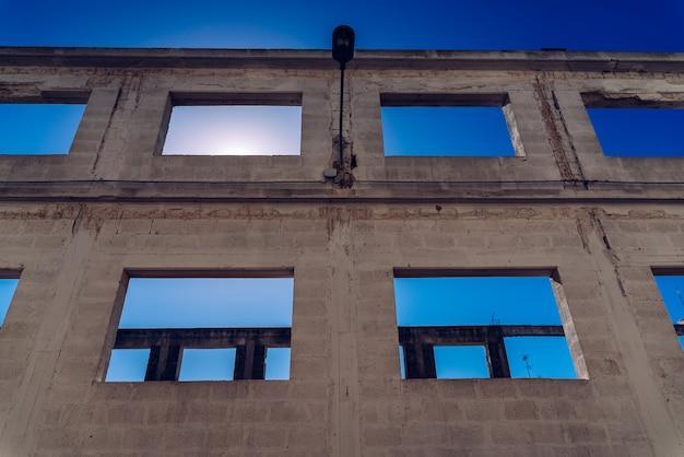 Fenêtre d'un bâtiment abandonné sans terminer sa construction, soleil intense et fond de ciel bleu profond.