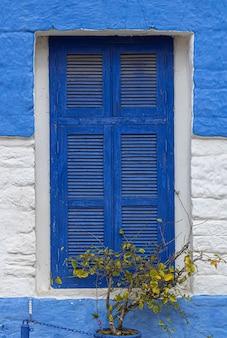 Fenêtre blanche et bleue d'une maison historique dans la médina du centre historique d'asilah au maroc