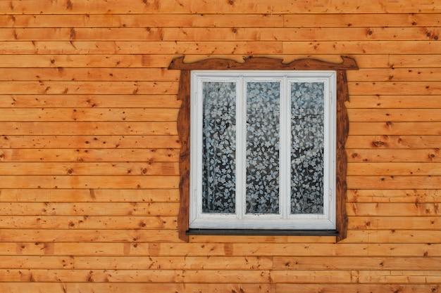Fenêtre en bois blanc dans le mur de planches de bois brun brut avec des nœuds. vue frontale. fermer.