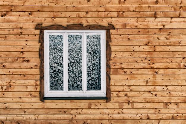 Fenêtre en bois blanc dans le mur de planches de bois bruts bruts avec noeuds.