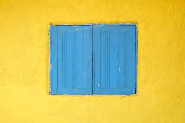 Fenêtre en bois bleue sur fond jaune