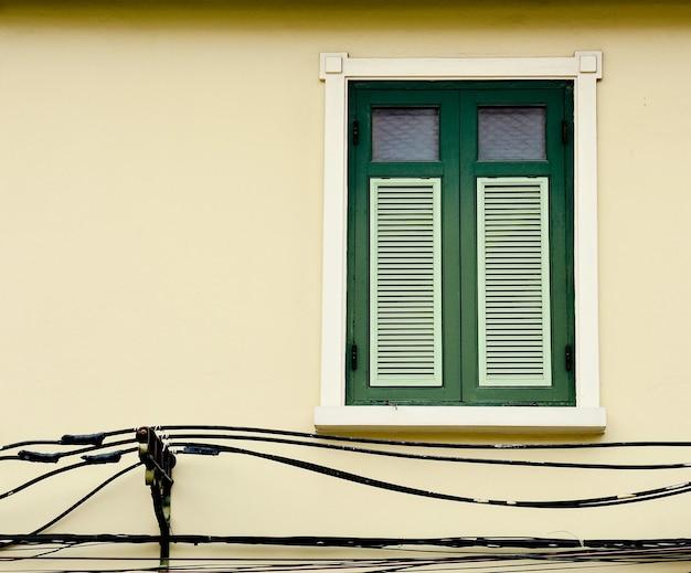 Fenêtre en bois vert antique au bâtiment en béton