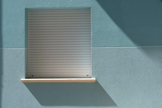 Fenêtre carrée avec une ombre du soleil sur un mur bleu