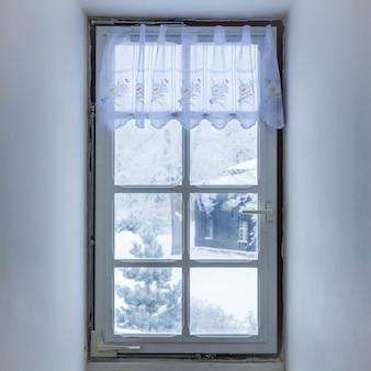 Fenêtre dans la pièce recouverte de mosaïque givrée en hiver. motifs de givre sur verre