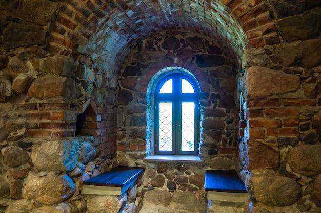 Fenêtre dans la salle intérieure du château médiéval en pierre.