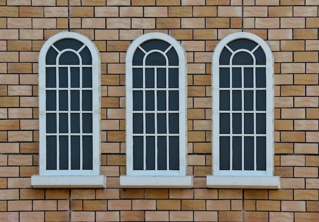 Fenêtre de design vintage classique sur tanné fond de mur de briques rouges.