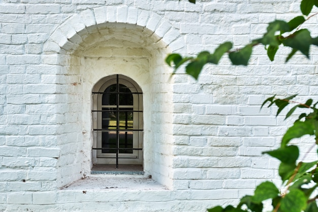 Fenêtre étroite dans le mur de briques peintes d'un ancien bâtiment d'un monastère russe