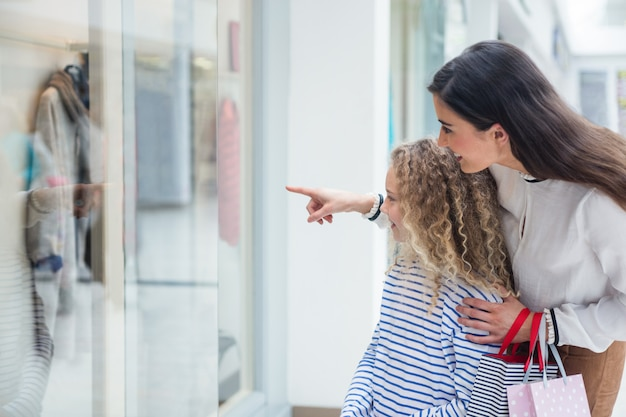 Fenêtre famille heureuse faire du shopping dans le centre commercial