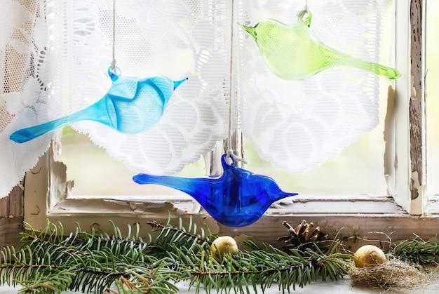 Fenêtre intérieure avec oiseaux en verre et arbre de noël