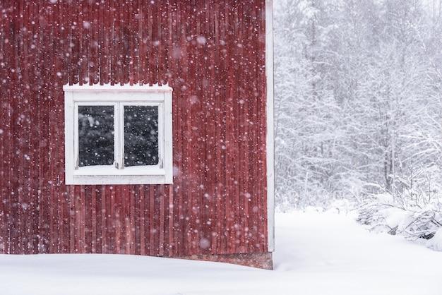 La fenêtre d'une maison dans la forêt s'est recouverte de neige épaisse et de mauvais ciel en hiver à tuupovaara, en finlande.
