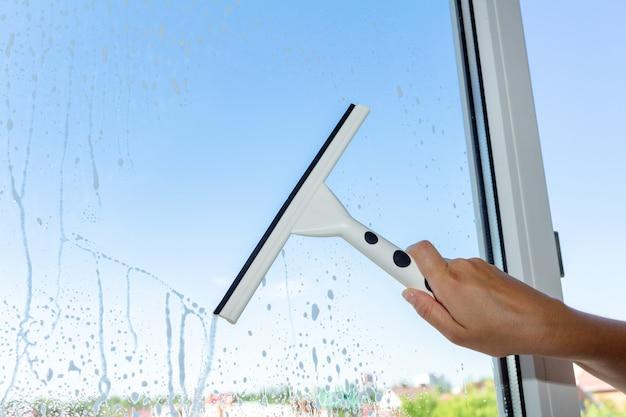 Fenêtre de nettoyage avec une brosse spéciale sur le ciel bleu