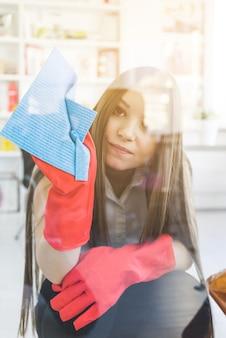 Fenêtre de nettoyage de femme de bureau triste