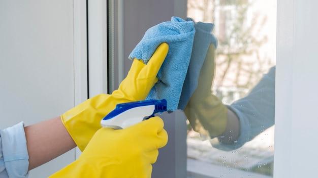Fenêtre de nettoyage en gros plan avec pulvérisation chimique