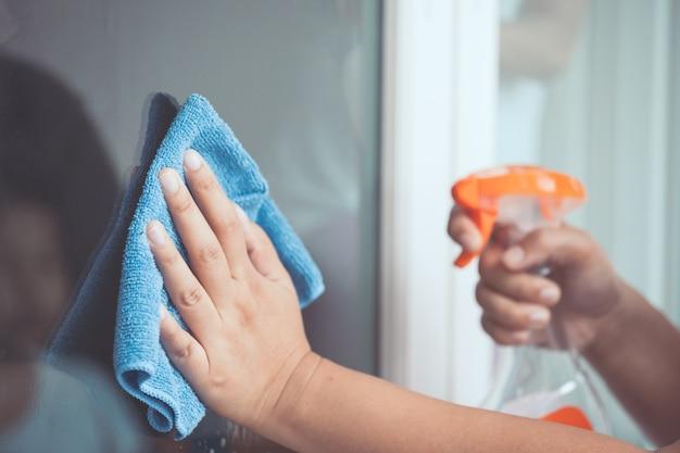 Fenêtre de nettoyage des mains de femme avec un chiffon et un spray nettoyant