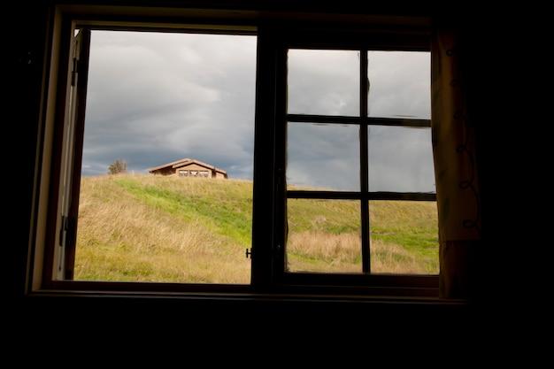 Fenêtre ouverte sur le pâturage avec le sommet d'une habitation visible sur une colline