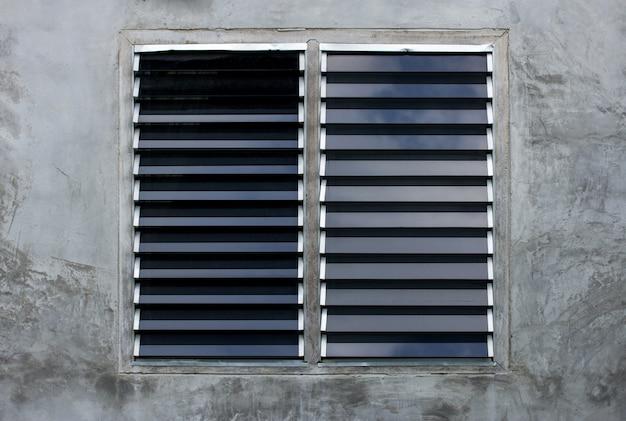 Fenêtre à persiennes sur un mur de béton gris