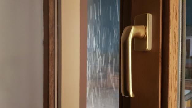 Fenêtre en plastique marron fermée dans la maison. gros plan sur un stylo. stratification de film de verre à vitre, un paquet de bois brun clair.