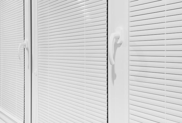 Fenêtre avec stores blancs horizontaux fermés