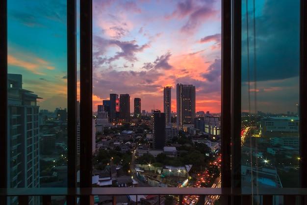 Fenêtre en verre dans la chambre avec vue au beau coucher de soleil. image de fond de paysage urbain.