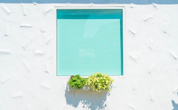 Fenêtre en verre sur un mur blanc avec pot de fleur