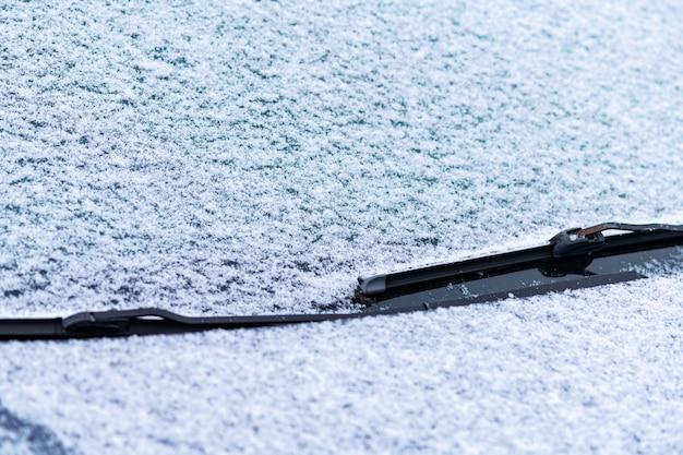 Fenêtre de voiture enneigée avec essuie-glaces
