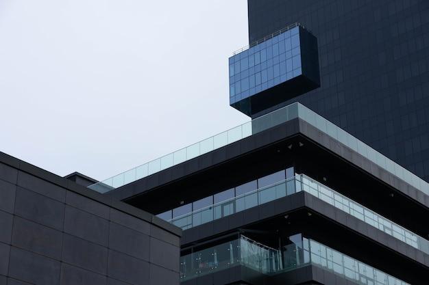 Des fenêtres noires, la façade d'un immeuble de bureaux moderne, un centre commercial dans une mégapole.